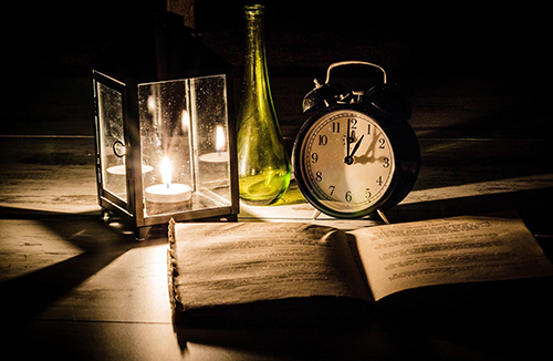 Image of a clock, a candle and a book